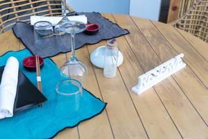 """Ansprechend gedeckter, reservierter Tisch mit Essstäbchen und weißem Holzsteller """"RESERVE"""""""