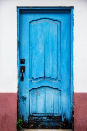 Antike blaue Holztür mit rot-weißer Hausfassade