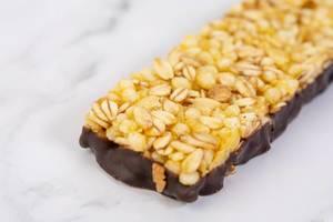 Antioxidant-Müsliriegel mit Orangengeschmack und Schokoladenüberzug, auf einem weißen Tisch
