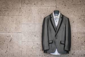 Anzug des Bräutigams in grau und schwarz mit weißem Hemd hängt auf Kleiderbügel an Wand