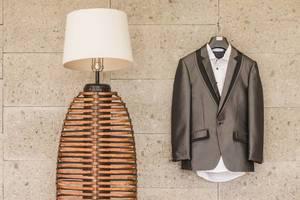Anzug des Bräutigams mit weißem Hemd hängt auf Bügel an Wand neben moderner Lampe