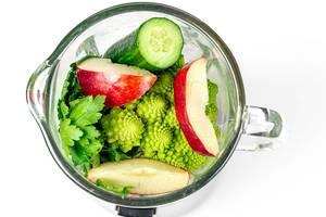 Apfelstücke, Petersilie, Kohl und Gurke in einem Mixer für einen grünen Smoothie mit weißem Hintergrund von oben fotografiert