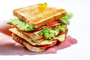Appetitanregendes Sandwich mit Kopfsalattomatenkäse und -schinken auf der Hand des Mannes