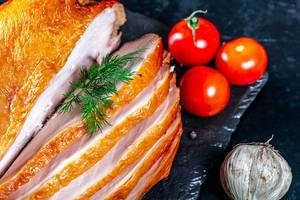 Appetizing pieces of smoked chicken with cherry tomatoes, garlic and dill on a black background