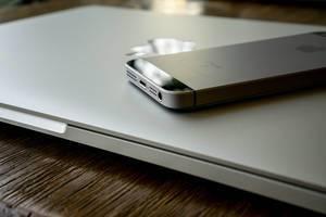 Apple iPhone auf MacBook Laptop auf Holztisch mit Reflektion