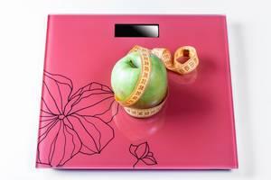 Apple umwickelt mit Maßband auf den Skalen als Symbol einer gesunden Ernährung