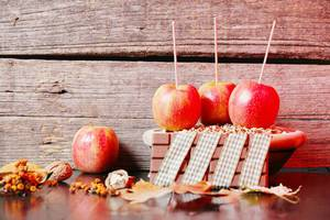 Apples and chocolate with walnuts, wooden background