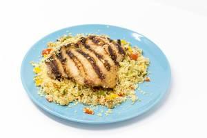 Arabisch gegrilltes Hähnchen auf Gemüsecouscous mit Razel Hanout Dip auf blauem Teller