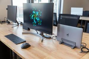 Arbeitsplatz am Schreibtisch im gemeinschaftlichen Arbeitsraum des WeWork Co-Working Space in Köln, mit LG-Bildschirm