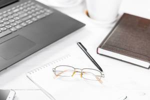 Arbeitstisch mit Utensilien wie Laptop, Schreiber, Notizheft, Smartphone, Kalenderbuch und Brille