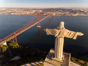 Areal view / drone shot from behind of Cristo Rei monument with Ponte 25 de Abril bridge in Almada Lisbon