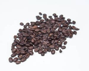 Aromatisch dunkel geröstete Kaffeebohnen auf weißem Hintergrund