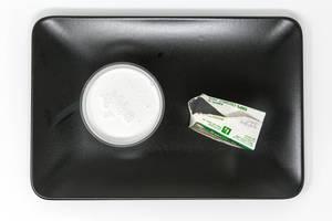 Aroy D - Kokosnussmilch im glas mit Verpackung auf schwarzem Teller - Aufsicht