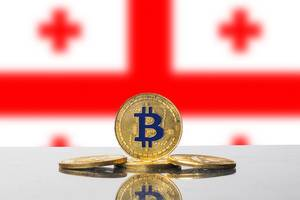 Arrangement aus vier goldenen Bitcoins vor der weiß-roten Flagge Georgiens