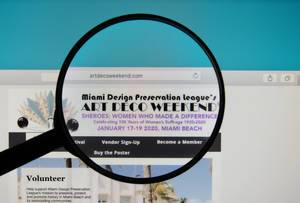 Art Deco Weekend website on a computer screen with a magnifying glass