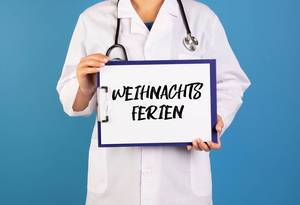 Arzt hält ein Schild mit der Schrift