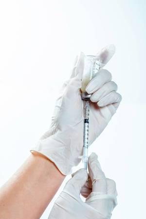 Arzt in weißen Gummi-Handschuhen zieht Spritze mit Medikamenten aus Ampulle auf