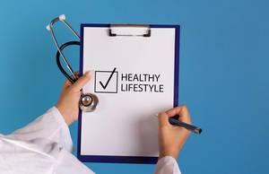 Arzt mit einem Stethoskop in der Hand hält ein Schild mit der Schrift