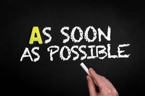 """ASAP: Hand schreibt  """"As soon as possible"""" - So bald wie möglich - mit Kreide auf eine schwarze Tafel"""