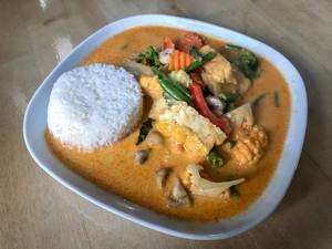 Asian Lunch with tofu thai and spicy curry sauce, coconut milk, rice, cream and fresh vegetables on a wooden table