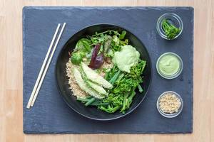 Asian lunch with wooden chopsticks and Green avocado bowl