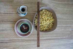 Asiatisches Frühstück aus Schüssel mit Nudeln, Essstäbchen und Tee auf Holztisch von oben fotografiert