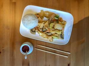Asiatisches Gericht mit Hühnchen, Pilzen, Karotten und weiterem Gemüse in Currysoße, dazu Reishügel auf Teller, Chilipaste in weißem Gefäß und Essstäbchen auf Holztisch