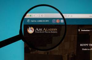 Ask Aladdin website on a computer screen with a magnifying glass