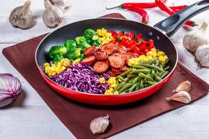 Asparagus, Brussels sprouts, corn, peppers and sausages in a frying pan (Flip 2019)