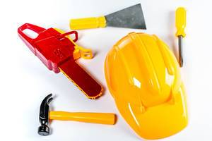 Assorted plastic toy tools and yellow helmet over white background (Flip 2019)