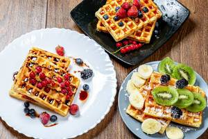 Assortment beautiful serve waffles with berries, fruits and syrups