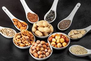 Assortment of nuts and seeds in white bowls and spoons on a black background, close- up (Flip 2020)