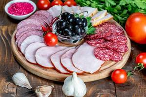 Assortment of sliced smoked sausages, salami and ham with vegetables (Flip 2019)