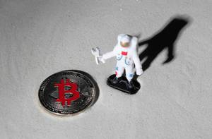 Astronaut and silver Bitcoin on the moon