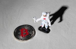 Astronaut und silberne Bitcoin-Münze auf dem Mond