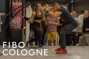 """Athlete and sports fair visitor trains with a Battlerope, next to the picture title """"Fibo Cologne"""""""