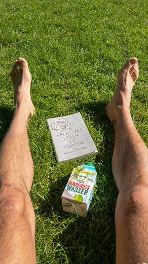 Auf dem Rasen liegen mit Buch und Kokosnusswasser