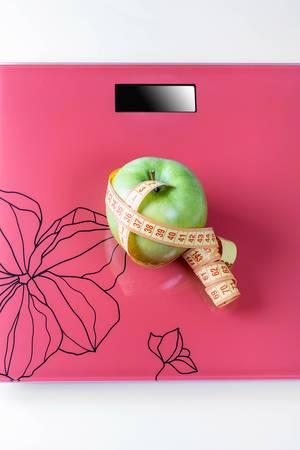 Auf der Waage ist ein Maßband und ein grüner Apple das Konzept des Gewichtsverlusts