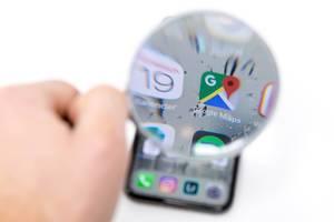 Auf Mobiltelefon durch Lupe betrachtetes Google Maps Icon neben Kalender App Logo