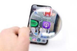 Auf Mobiltelefon durch Lupe betrachtetes Podcast App Logo neben Spotify Icon vor weißem Hintergrund