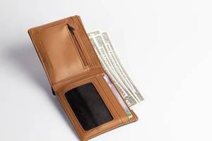 Aufgeklappte verlorene Geldbörse mit Geldscheinen und Bankkarten isoliert vor weiß