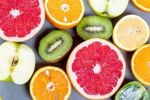 Aufgeschnittene, halbierte Äpfel, Kiwis, Orangen und Grapefruits aus der Sicht von oben