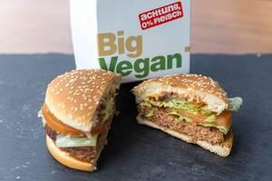Aufgeschnittener Big Vegan TS Burger von McDonalds mit Bratling auf Soja- und Weizeneiweißbasis vor dem Verpackungskarton