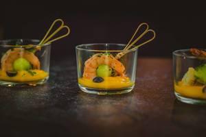 Aufgespießte Schrimps in Mango-Soße garniert mit schwarzen und grünen Oliven - Nahaufnahme in Seitenansicht