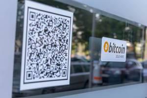 Aufkleber Bitcoin sold here und Barcode auf einem Fenster