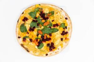Aufnahme von oben der Yoga-Pizza Vegan von Followfood mit Bio-Dinkelboden, ausgewähltem Bio-Gemüse, Hummussauce und ayurvedischen Gewürzen von Herbaria