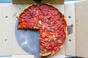 Aufnahme von oben: drei Viertel einer typischen Chicago Deep Dish Pizza von Pizzeria Uno mit Käse und Tomaten und mit hohem Rand