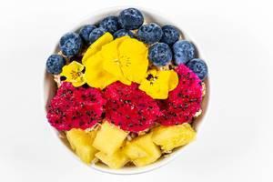 Aufnahme von oben: frische Stücke Pitahaya, Ananas, Blaubeeren und Blumen mit Haferflocken in einer Schüssel vor weißem Hintergrund