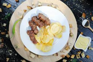 Aufnahme von oben: gegrillte Hackfleischstücke mit runden frittierten Kartoffelscheiben