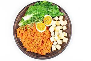 Aufnahme von oben: Gemüse mit gekochtem Ei, Käsewürfel und Zucchinikaviar auf einem braunen Teller vor weißem Hintergrund